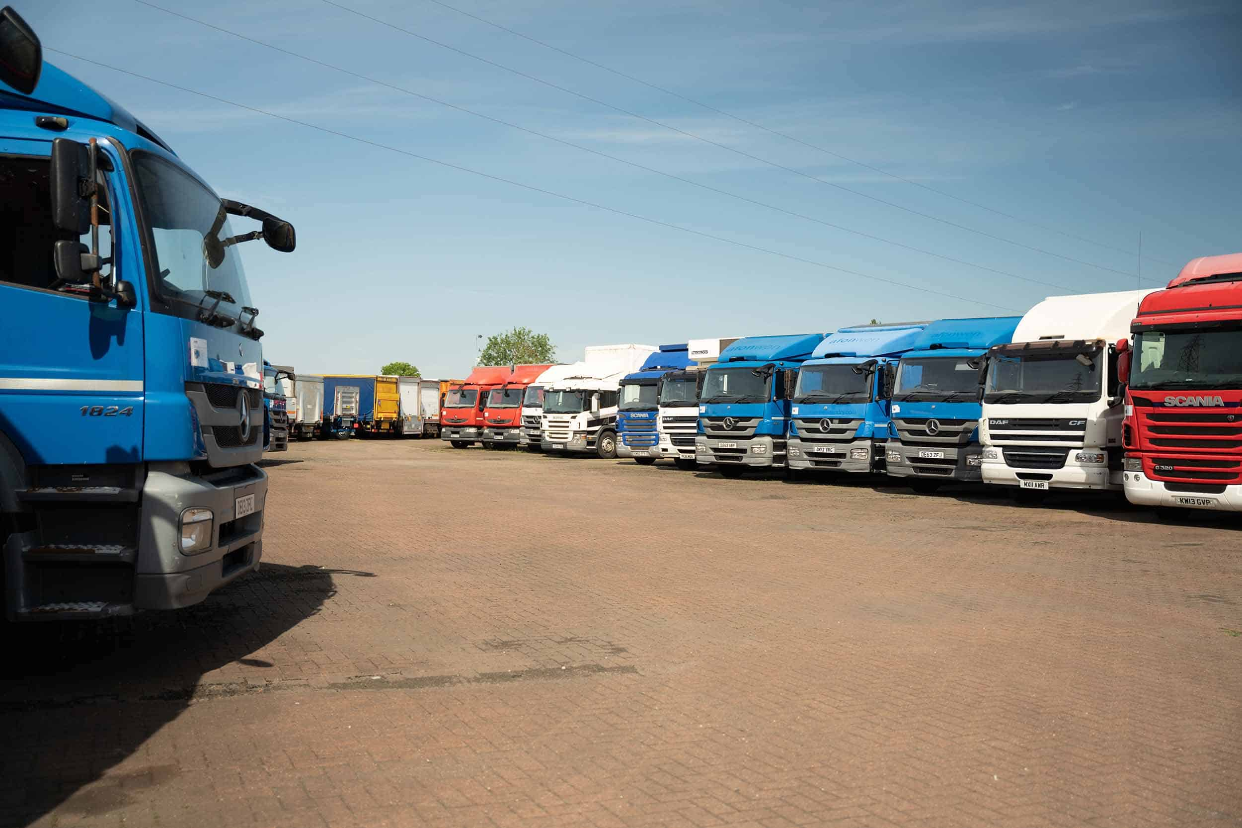 a large selection of used heavy goods vehicles in a forecourt, parked in an orderly fashion
